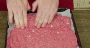 Han legger kjøttdeig på bakepapir og putter det i ovnen. Mot slutten vil du gjøre det samme.