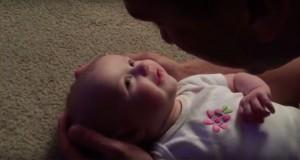 Faren holder babyen, lener seg frem og begynner å synge. Babyens reaksjon er nydelig.