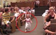Brudepiken hylgriner nedover kirkegulvet. Følg nå nøye med på hva som er bak henne.