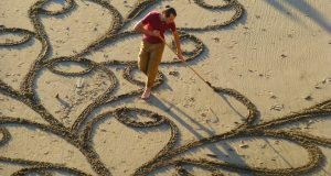 En mann bringer en enkel rive med seg til stranden. Og når du zoomer ut og ser det… HALSBREKKENDE.