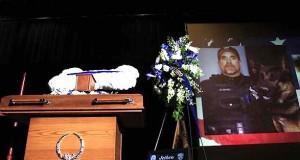 En elsket politioffiser ble drept – men legg merke til de hvite blomstene på kisten hans.