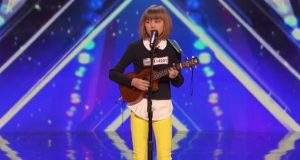 12-åringen står ved mikrofonen med sin ukulele. Hennes neste trekk lamslår hele bygningen.