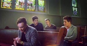 4 menn sitter i en tom kirke. Når de begynner å synge, renner tårene nedover kinnet mitt.