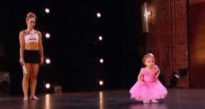 Den 2 år gamle jenta blir med mammaen sin opp på scenen. Hold et øye med føttene hennes.