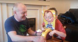 Den lille gutten legger ansiktet sitt i masken. Men hold et øye med bestefaren. For en skøyer!