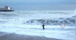 Kvinne risikerer livet for å redde hunden sin fra det stormfulle havet.